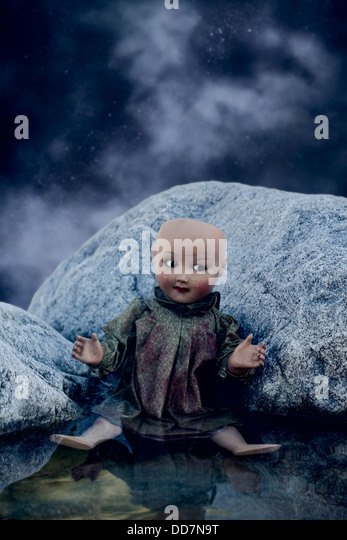 a broken doll sitting in the water - Stock Image