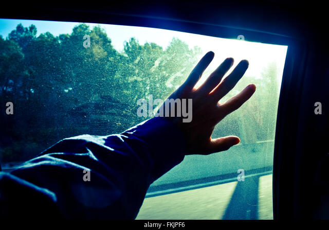 A hand on a glass of a window. - Stock Image