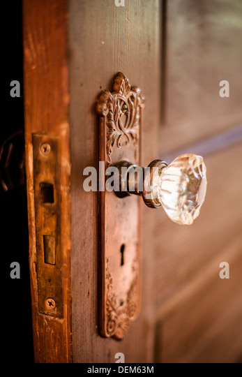 Closeup of an antique wooden door in the interior of a home with a glass doorknob and skeleton key hole. - Stock Image