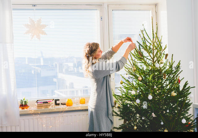 Finland, Helsinki, Woman decorating christmas tree - Stock Image