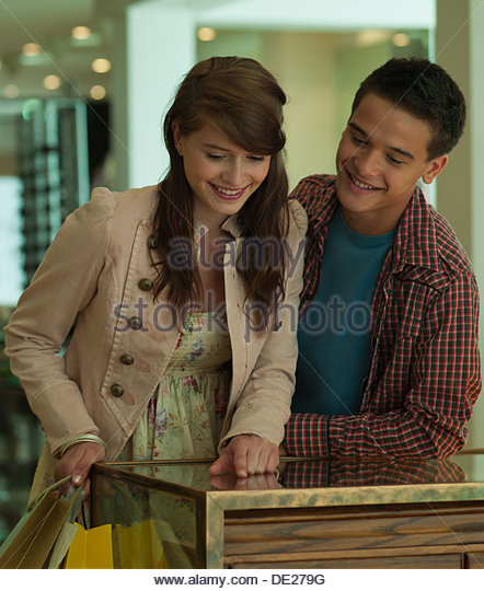 Smiling teenage couple looking in display case - Stock-Bilder