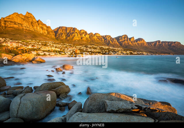 Sunset in Camps Bay with Table Mountain on the left and the Twelve Apostles to the right, Western Cape, South Africa - Stock Image