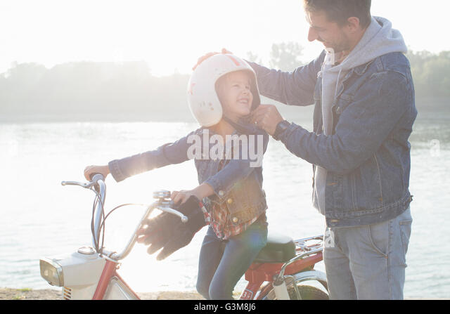 Young girl sitting on father's moped, father putting crash helmet on daughter's head, smiling - Stock Image