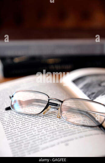 Reading glasses on top of book of antiquity - Stock-Bilder