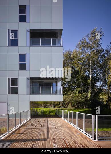 Exterior facade showing reflective glass cladding and walkway over river. Dunluce Apartments, Ballsbridge, Ireland. - Stock-Bilder