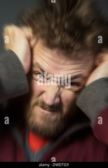 An angry man tearing his hair out - Stock Image