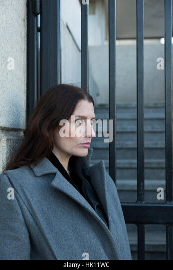 An attractive woman with long dark hair stares away whilst situated against a set of railed gates. - Stock Image