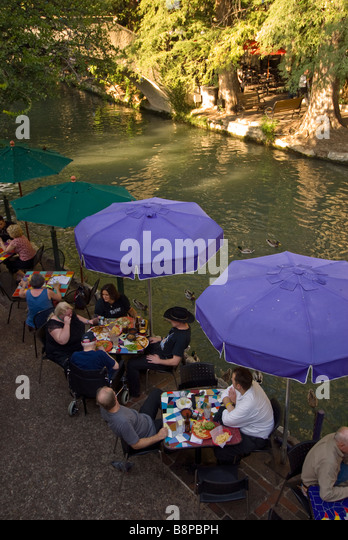 San Antonio River Walk riverwalk blue umbrellas diners dining - Stock Image
