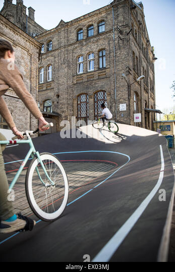 Male and female cyclists racing uphill on city velodrome, Riga, Latvia - Stock Image