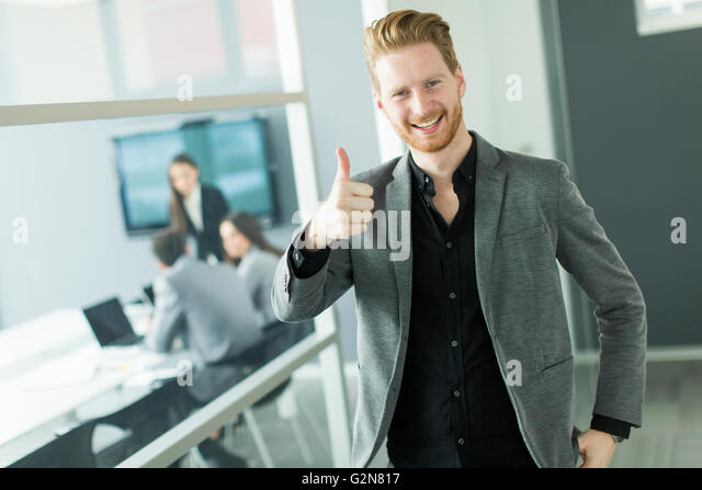 Young businessman showing thumb up - saying okay - Stock Image