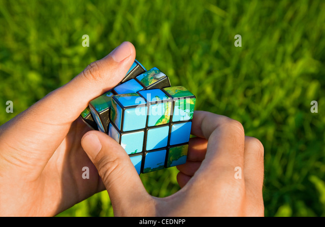 Cube in the manner of planets land in hand on background of the herb - Stock Image