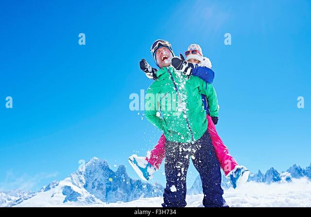 Father giving daughter piggyback ride, Chamonix, France - Stock Image
