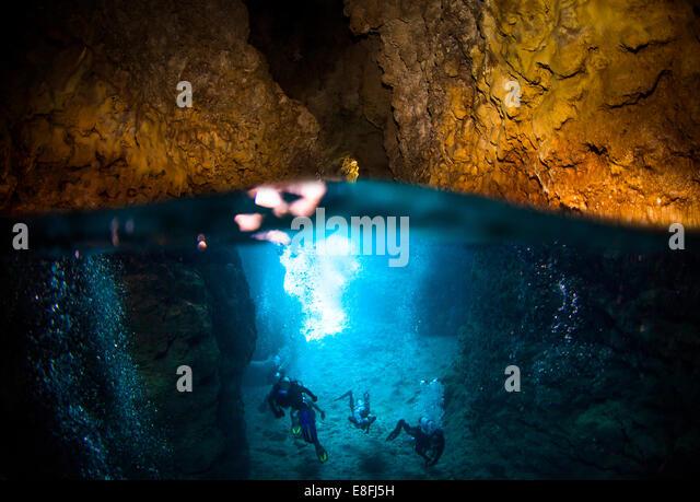 Four Scuba divers exploring Blue Cave, Okinawa, Japan - Stock Image