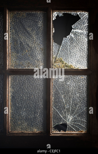 An old window with two of its panes broken - Stock Image