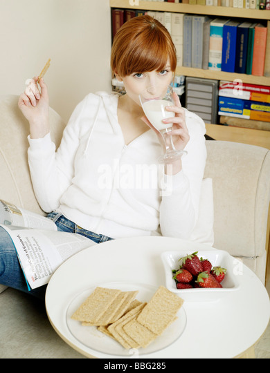 1253773 people one girl 15 20 20 25 youg adult red haired fringe white blouse hood sit coach read newspaper magazine - Stock-Bilder
