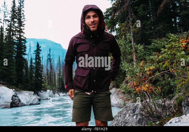 Mid adult man river wearing hooded waterproof coat camera smiling Moraine lake Banff National Park Alberta Canada - Stock Image