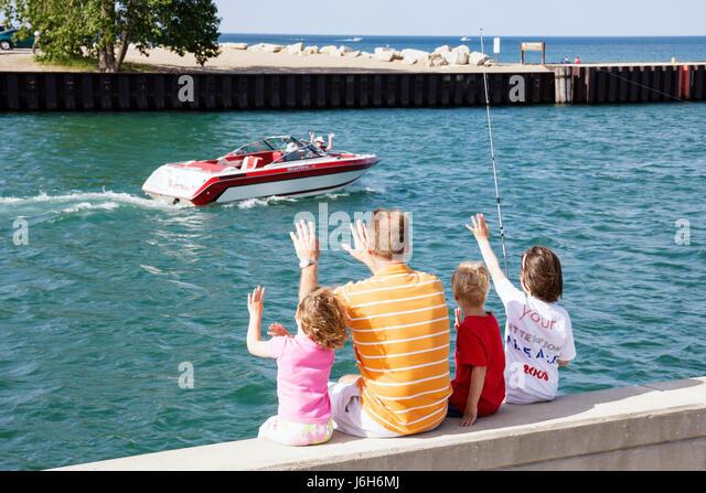 Wisconsin Kenosha Lake Michigan Harbor Park man girl parent child family fishing outdoor activity boat wave - Stock Image