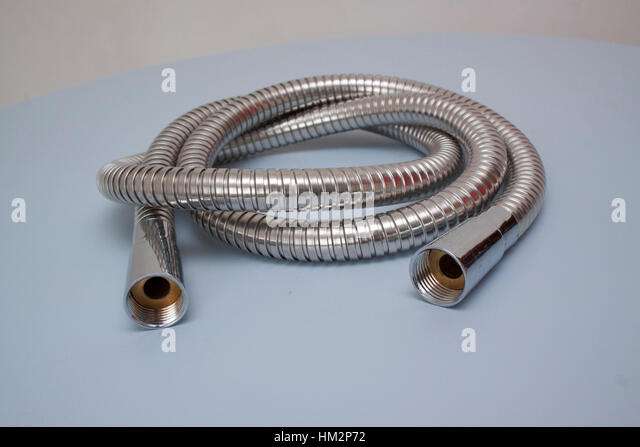 Spiral flexible metal shower hose on a pale blue background - Stock Image
