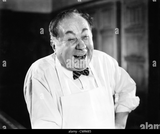 1930s 1940s LAUGHING MAN PORTRAIT WEARING APRON BUTCHER BAKER GROCERY CLERK SERVICE HAPPY MAN - Stock Image