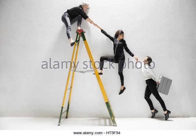 Businesswomen holding hands, helping lift each other on ladder - Stock-Bilder