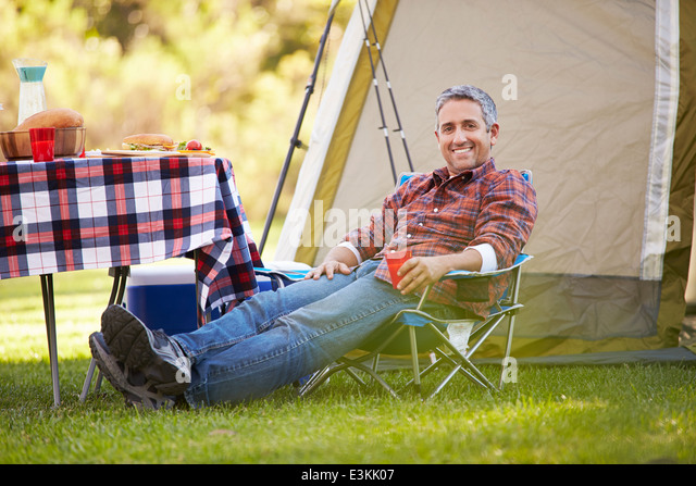Man Enjoying Camping Holiday In Countryside - Stock Image