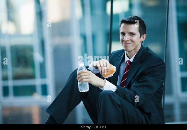 Caucasian businessman eating lunch - Stock Image