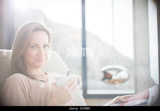 Woman having cup of coffee on sofa - Stock Image