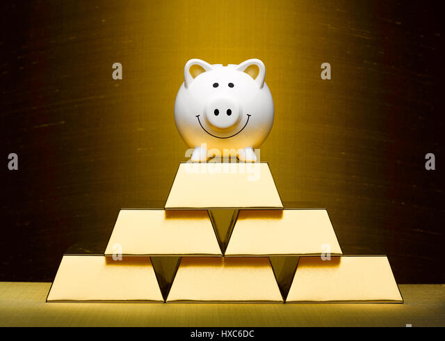 Smiling piggy bank on top of stacked gold bars - Stock Image