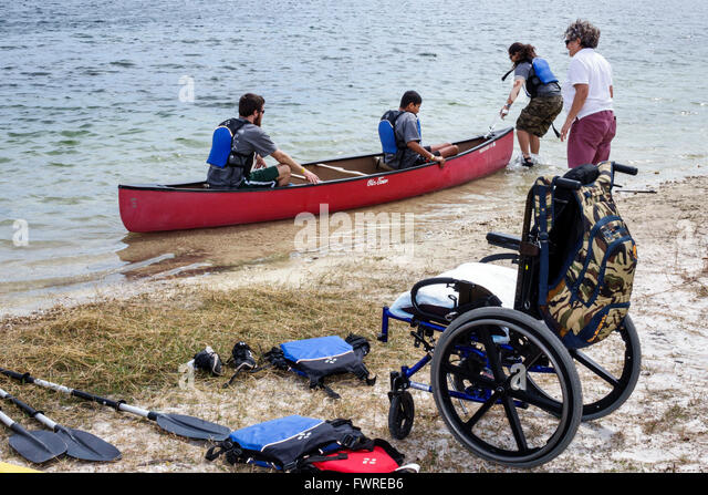 Florida FL Miami Tropical Park Paralympic Experience sports volunteer helping Hispanic teen boy disabled wheelchair - Stock Image