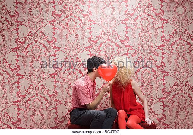 Couple behind heart shaped balloon - Stock-Bilder