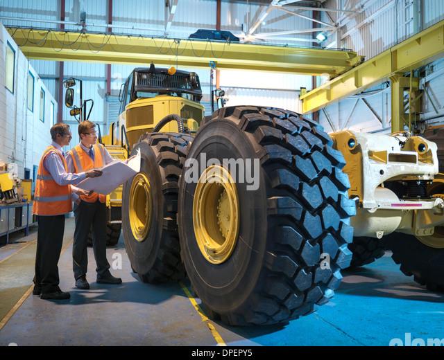 Engineers with engineering drawings inspecting heavy truck - Stock-Bilder