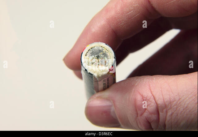 A leaking/corroded 1.5V AA battery (as used in the UK). - Stock Image