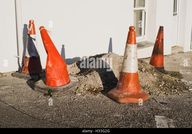 Red and white traffic cones surrounding a mound of waste on a roadside - Stock Image