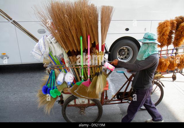 Bangkok Thailand Ratchathewi Pratunam street vendor cleaning brushes brooms tricycle - Stock Image