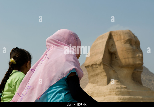 Local egyptian girls looking at thehead of the Great Sphinx of Giza, Cairo Egypt - Stock Image