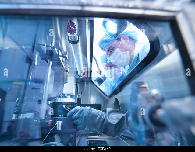 Electronics workers looking into sealed work station window in clean room laboratory - Stock Image