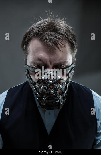 Furious man in muzzle over grey - Stock Image
