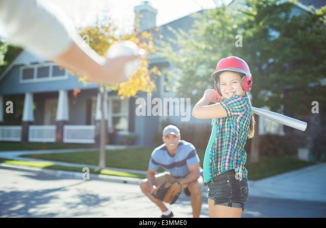 Family playing baseball in street - Stock-Bilder