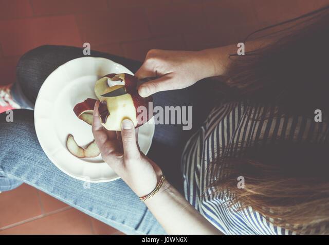 Girl peeling an apple - Stock Image