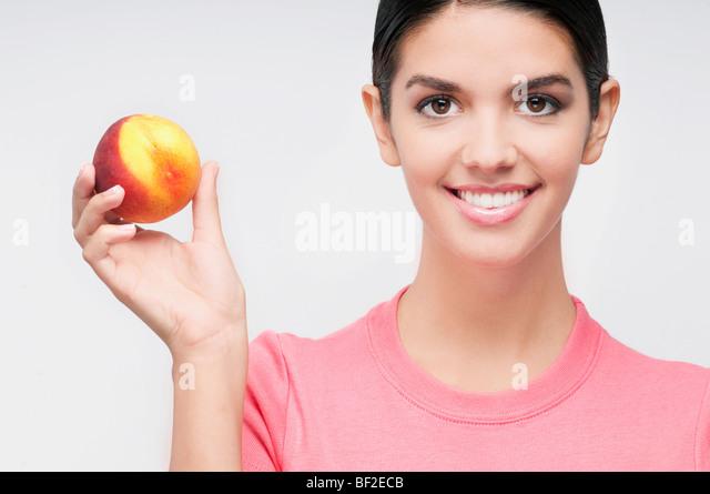 Portrait of a woman holding a peach - Stock-Bilder