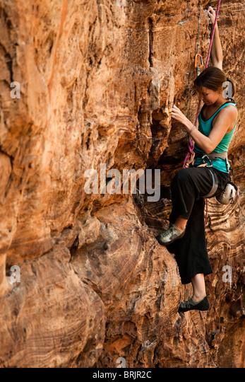 Caucasian female climber in a blue singlet climbing a sandstone cliff in Badami, India. - Stock-Bilder