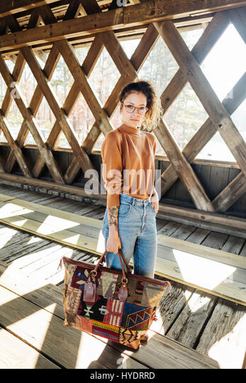 Young beautiful girl with curly hair and glasses standing  with handbag in a covered bridge - Stock Image