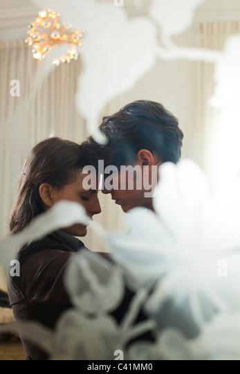 Couple embracing, viewed through window - Stock-Bilder