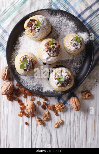 Homemade baked apples with raisins, walnuts and honey on a plate vertical view from above - Stock Image