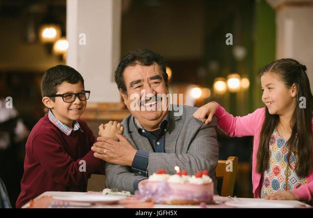 Hispanic grandchildren celebrating birthday of grandfather in restaurant - Stock Image