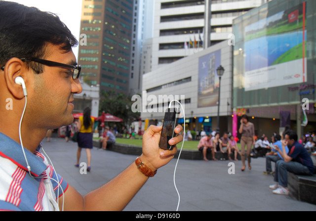 Singapore Raffles Place central business financial district plaza Asian man smart phone - Stock Image