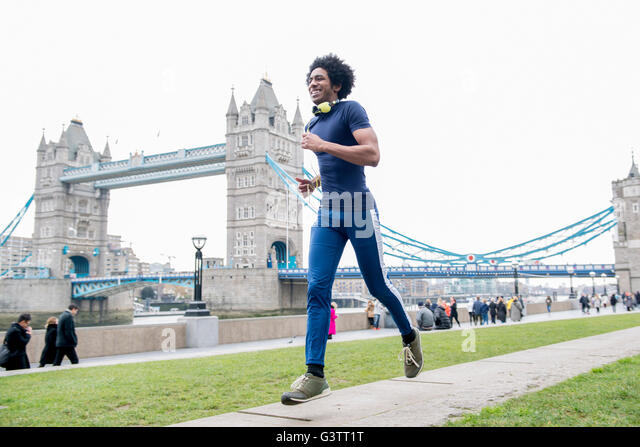 A young man jogging past Tower Bridge in London. - Stock-Bilder