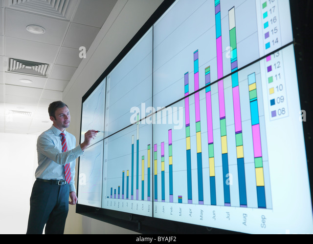 Businessman with graphs on screen - Stock Image
