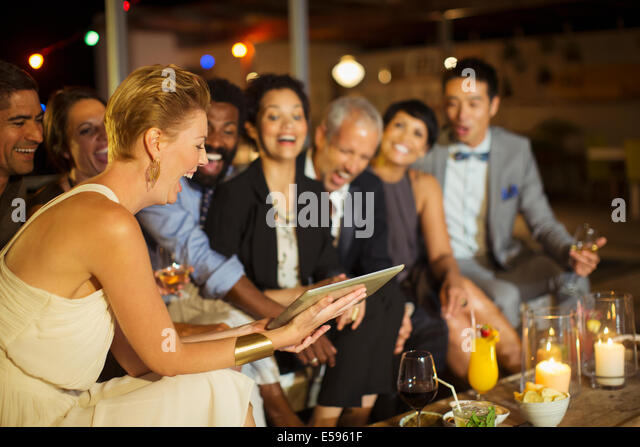 Friends using digital tablet at party - Stock-Bilder