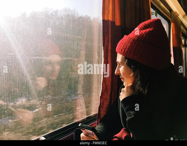 Young Woman Wearing Knit Hat Sitting In Train - Stock Image
